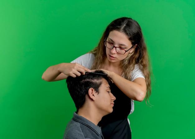 緑の壁の上に立っている男性クライアントの髪をとかすエプロンの若いプロの美容師の女性