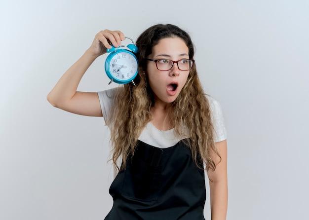 目覚まし時計を保持しているエプロンの若いプロの美容師の女性は、白い壁の上に立って驚いて驚いて脇を見ています