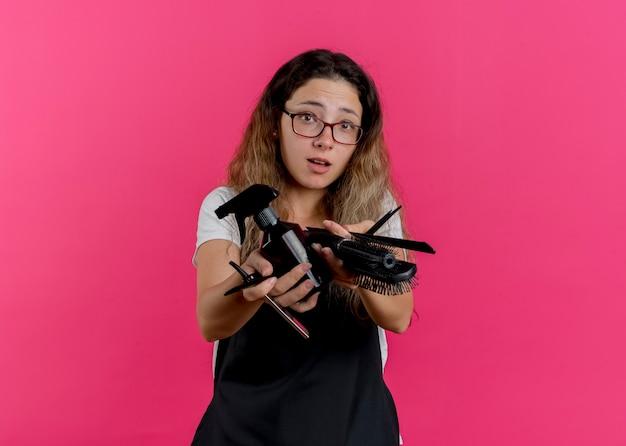 ピンクの壁の上に立って混乱している正面を見て、コームスプレーとスプレーでかみそりを保持しているエプロンの若いプロの美容師の女性