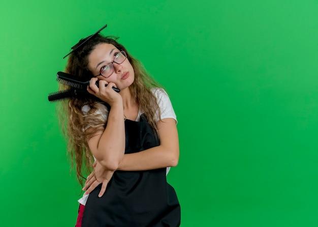 困惑して見上げるヘアブラシを保持しているエプロンの若いプロの美容師の女性