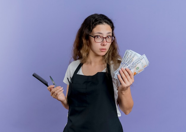 Молодой профессиональный парикмахер женщина в фартуке держит в замешательстве расческу для волос, ножницы и деньги