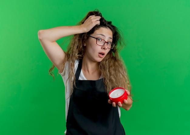 間違いのために彼女の頭の上の手と混同されたヘアクリームの瓶を保持しているエプロンの若いプロの美容師の女性