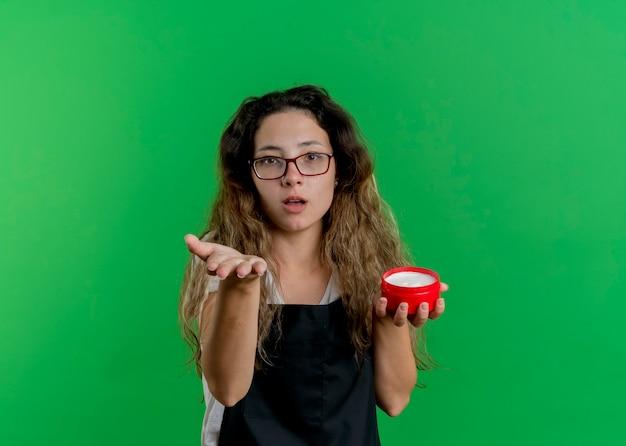 エプロンの若いプロの美容師の女性は、緑の壁の上に立って提供したり、尋ねたりするように腕を伸ばして正面を見てヘアクリームの瓶を持っています