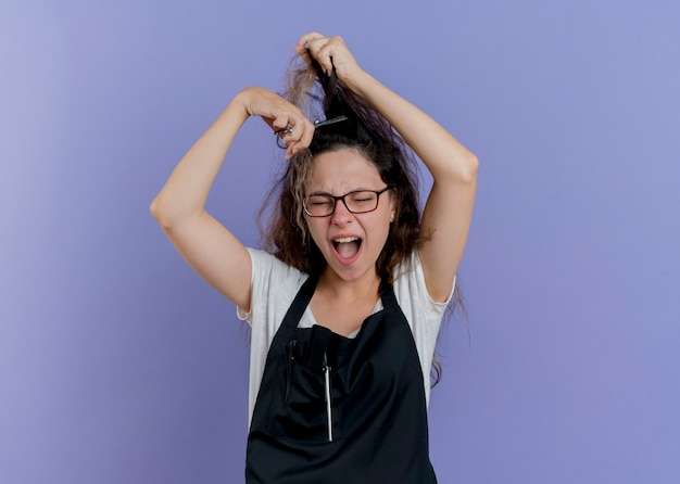青い壁の上に立っているイライラした表情で叫んで彼女の髪をカットしようとしているはさみを保持しているエプロンの若いプロの美容師の女性