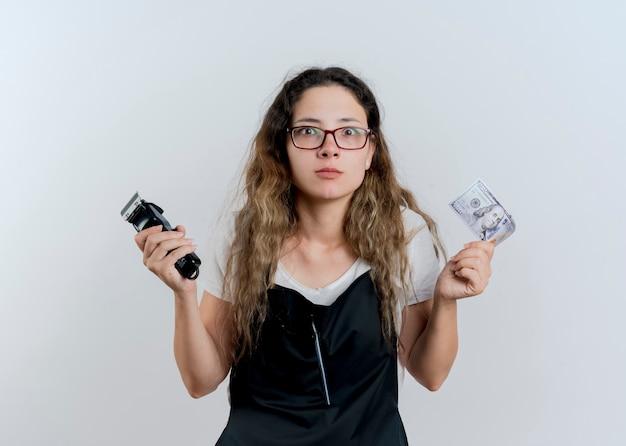 트리머와 현금을 들고 앞치마에 젊은 전문 미용사 여자는 흰 벽 위에 서 놀라게하고 놀란 전면을보고