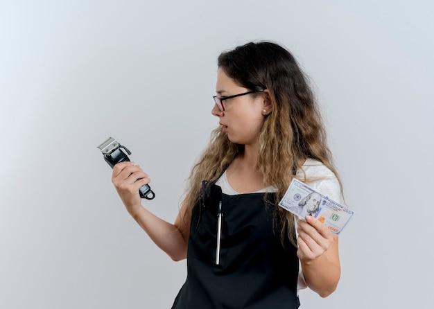 트리머와 현금을 들고 앞치마에 젊은 전문 미용사 여자는 흰 벽 위에 서 놀란 찾고