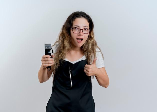 エプロンの若いプロの美容師の女性が白い壁の上に立って親指を見せて笑顔を正面に見てトリマーを保持しています