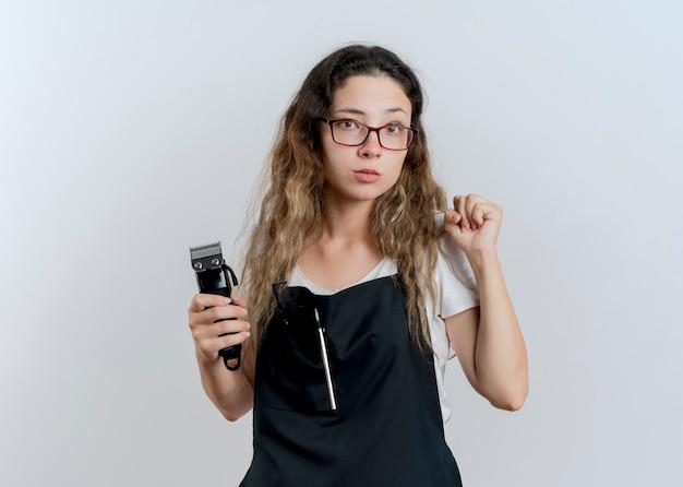 앞치마 지주 트리머에 젊은 전문 미용사 여자 심각한 얼굴 흰 벽 위에 서있는 주먹을 떨림으로 정면을보고