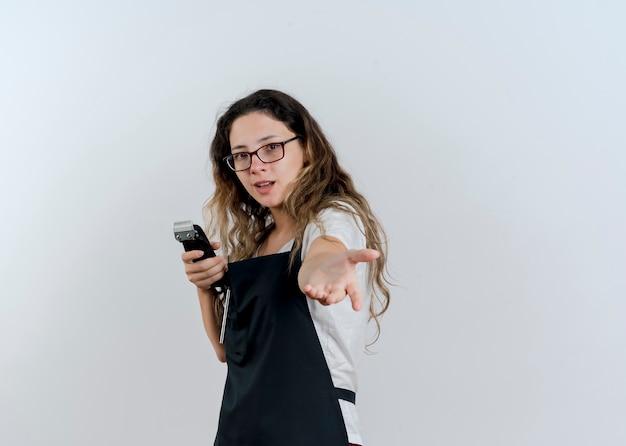 Молодой профессиональный парикмахер женщина в фартуке, держащая триммер, делает жест, приехавший сюда с рукой, улыбаясь, глядя на перед, стоя над белой стеной