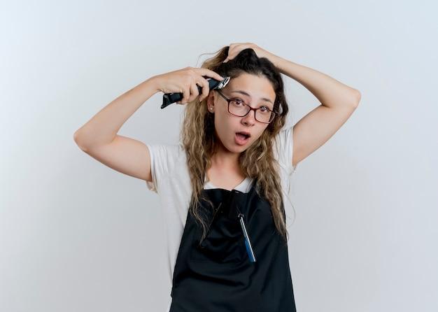 Молодой профессиональный парикмахер женщина в фартуке, держащая триммер, пытается подстричь волосы, выглядит удивленно, стоя над белой стеной