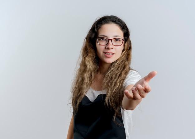 Молодой профессиональный парикмахер женщина в фартуке, глядя на фронт, предлагая руку, улыбаясь приветствующий жест, стоящий над белой стеной