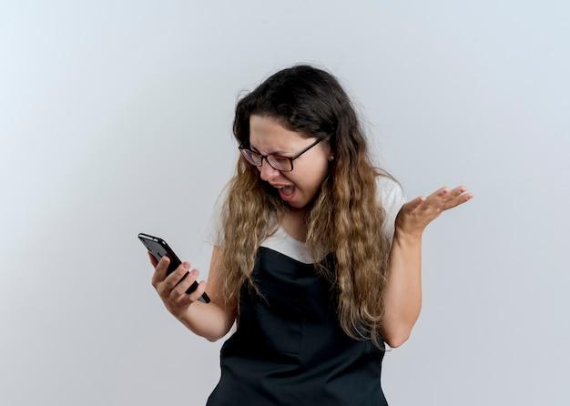 白い壁の上に立っている攻撃的な表情で野生の叫びに行く彼女のスマートフォンの画面を見ているエプロンの若いプロの美容師の女性