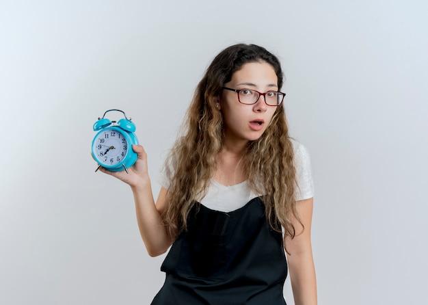 알람 시계를 보여주는 앞치마에 젊은 전문 미용사 여자는 흰 벽 위에 서 놀란 정면을보고