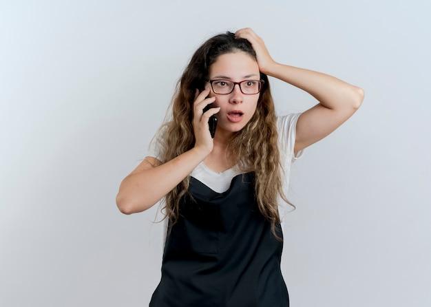 앞치마에 젊은 전문 미용사 여자는 흰 벽 위에 서 혼란되는 휴대 전화에 얘기