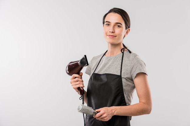 Young professional hairdresser in workwear holding hairbrush and hairdryer for making hairstyle while standing in isolation