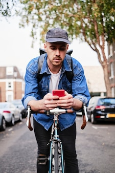 Young professional man standing with his bike and holding a phone outside.
