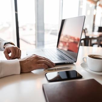 화창한 날 사무실에서 테이블에 앉아 노트북에서 작업하는 흰 셔츠에 젊은 전문 관리자 남자