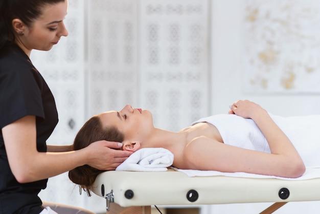 Молодой профессиональный массажист делая массаж для сонной кавказской женщины на предпосылке белой комнаты.