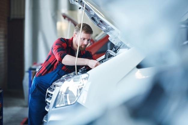 それを修理している間開いたエンジンを曲げる車修理サービスセンターの若いプロのマスター