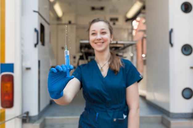 Young professional nurse in medical uniform show syringe in her hands at ambulance background
