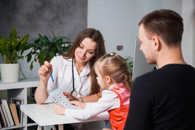 Молодой профессиональный педиатр показывает рецепты ребенку. детское шоу врачей советует маленькой девочке с отцом в офисе ее клиники