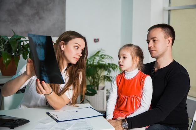 Молодой профессиональный педиатр показывает ребенку рентгеновский снимок черепа человека. детское шоу врачей советует маленькой девочке с отцом в офисе ее клиники