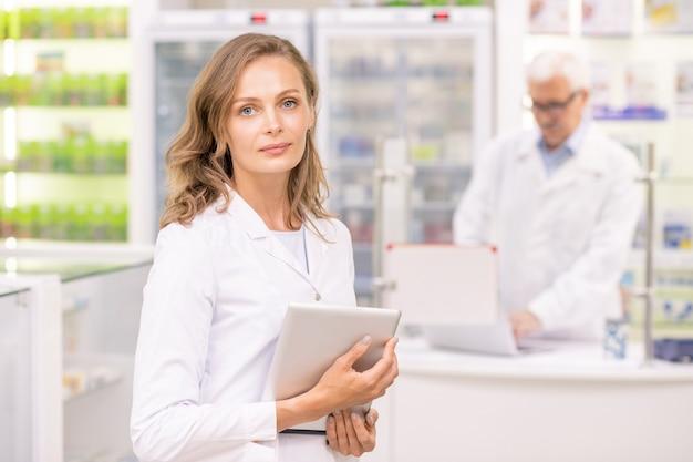 Молодой профессиональный фармацевт и помощник крупной аптеки с помощью сенсорной панели для поиска необходимых лекарств во время работы
