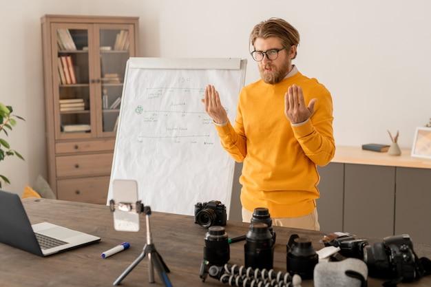 Молодой профессиональный фотограф в повседневной одежде смотрит на камеру смартфона и дисплей ноутбука во время разговора с онлайн-аудиторией