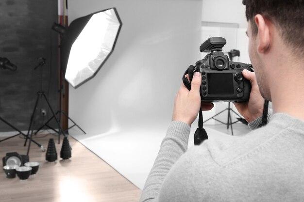 Молодой профессиональный фотограф с камерой в студии