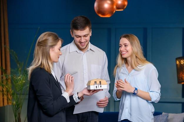 若いプロの不動産業者、スタイリッシュな青いオフィスでクライアントのカップルとの会議でデザイナー。