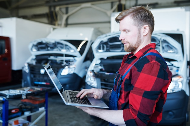 Young professional repairman of car service center using laptop while surfing on website or taking online orders