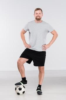 Молодой профессиональный футболист с ногой на мяч, стоящий перед камерой и смотрящий на вас изолированно