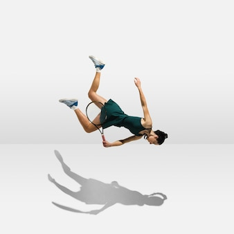 Young professional sportswoman levitating flying while playing tennis isolated on white wall
