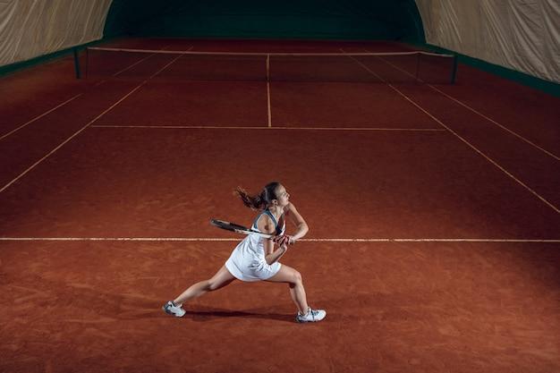Молодая профессиональная спортсменка играет в теннис на стене спортивной площадки