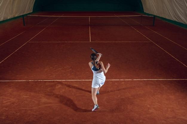 スポーツコートの壁でテニスをしている若いプロスポーツウーマン