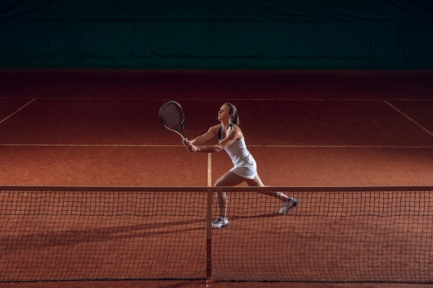 Young professional sportswoman playing tennis on sport court wall
