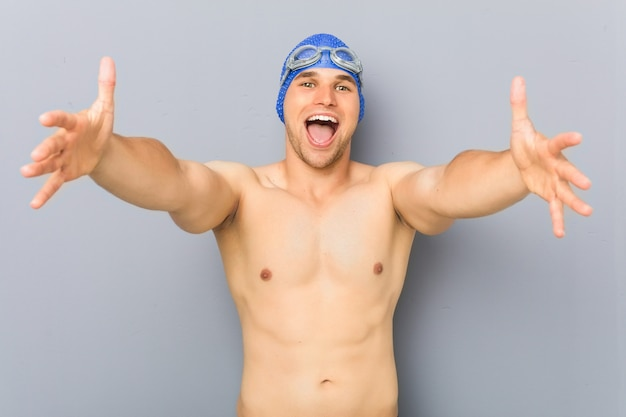 Young professional swimmer man feels confident giving a hug to the camera.