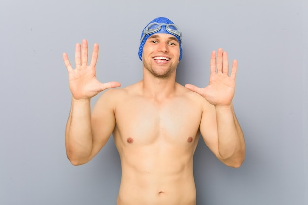 Young professional swimmer man showing number ten with hands.
