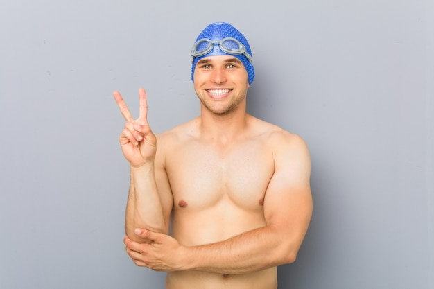 Young professional swimmer man showing number two with fingers.