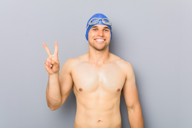 Young professional swimmer man showing victory sign and smiling broadly.