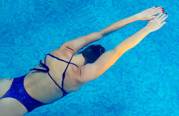 Young professional swimmer woman swimming in indoor pool