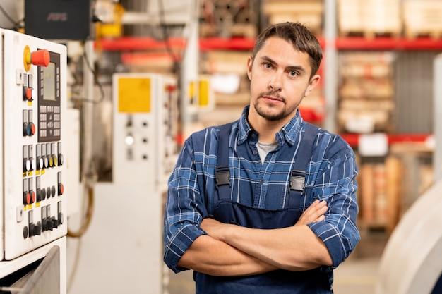 若い専門技術者または大規模な加工工場のエンジニアで、職場のそばに立っている間あなたを探しています