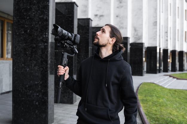 Молодой профессиональный видеооператор держит профессиональную камеру на 3-х осевой карданный стабилизатор. профессиональное оборудование помогает делать качественное видео без встряхивания. оператор носить черный балахон, делая видео.