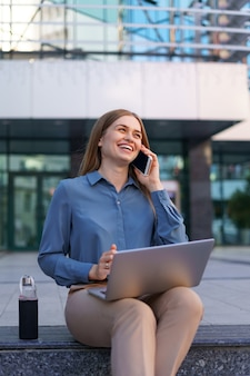 Молодая профессиональная женщина сидит на лестнице перед стеклянным зданием, держит ноутбук на коленях и разговаривает по мобильному телефону
