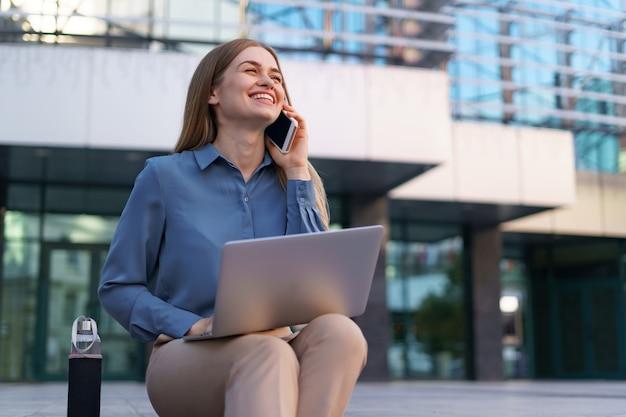 ガラスの建物の前の階段の上に座って、ラップトップを膝の上に置いて携帯電話で話している若い専門職の女性