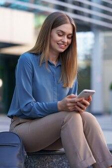 携帯電話で話しているガラスの建物の前の階段に座っている若い専門職の女性