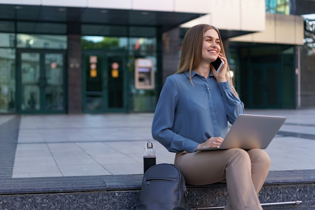 Young professional woman sitting on stair in front of glass building, holding laptop in lap and talking on mobile phone