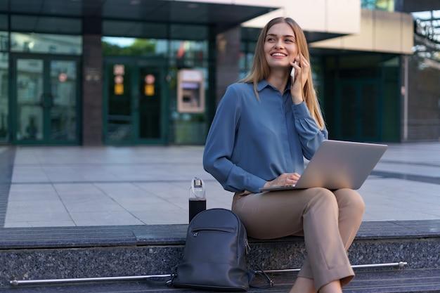 Giovane donna professionale che si siede sulla scala davanti all'edificio di vetro, tenendo il laptop in grembo e parlando al telefono cellulare