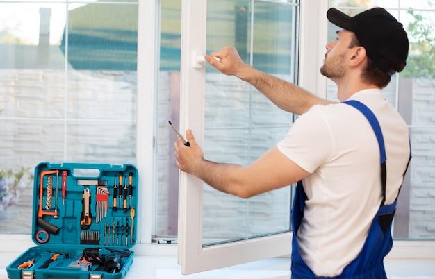 Молодой профессиональный рабочий человек в униформе устанавливает окно с помощью инструментов
