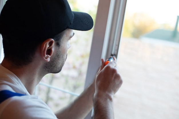 Young professional worker man in uniform suit is installing window with help of tools